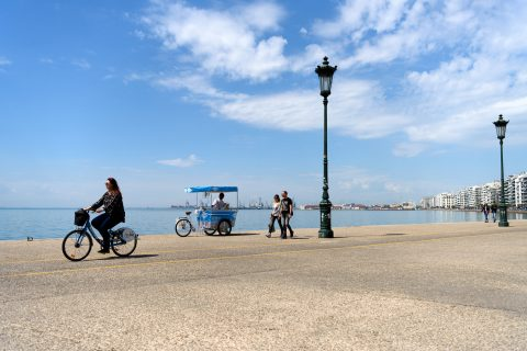Thessaloniki Greece - April 14 2017 : Woman riding an iBike at the seafront of the northern Greek city of Thessaloniki with ice cream vendor cart in background